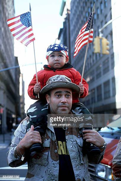 Veterans' Day Parade up Fifth Avenue in Manhattan A child waves two American flags as he sits on his father's shoulders during the parade