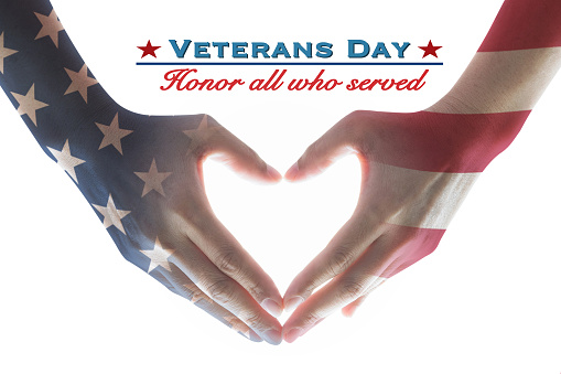 USA Veterans day with United Stated of America flag pattern on people's hands in heart shape and greeting announcement honoring all who served American country 1180882297