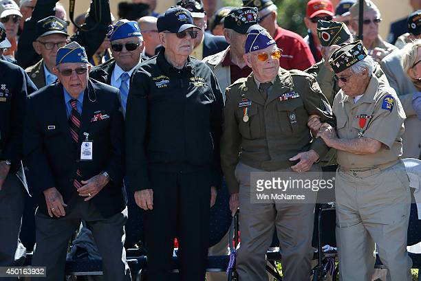 Veterans help each other stand up for a round of applause at a ceremony with US President Barack Obama at the Normandy American Cemetery on the 70th...