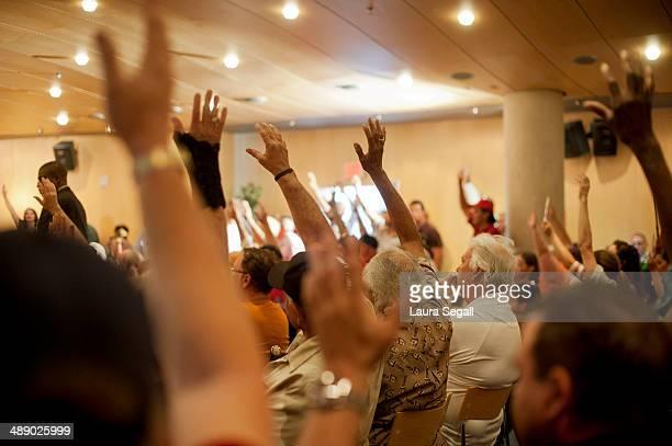 Veterans raise their hands as Sen John McCain speaks at a forum at the Burton Barr Central Library on May 9 2014 in Phoenix Arizona Sen John McCain...