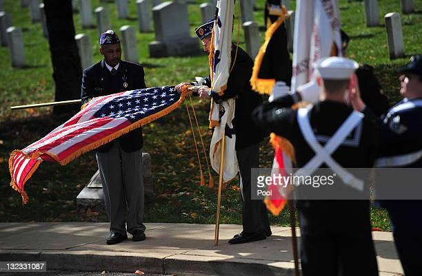 Veterans roll up a flag following a Veteran's Day ceremony at Arlington National Cemetery November 11 2011 in Arlington Virginia President Barack...
