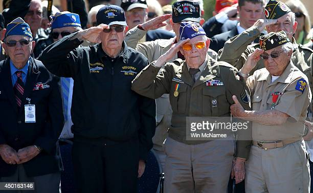 Veterans salute during the playing of 'Taps' at a ceremony with US President Barack Obama at the Normandy American Cemetery on the 70th anniversary...