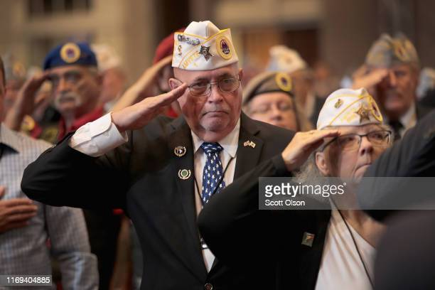 Veterans salute for the presentation of colors during the Joint Opening Ceremony at the American Veterans 75th National Convention at the Galt House...