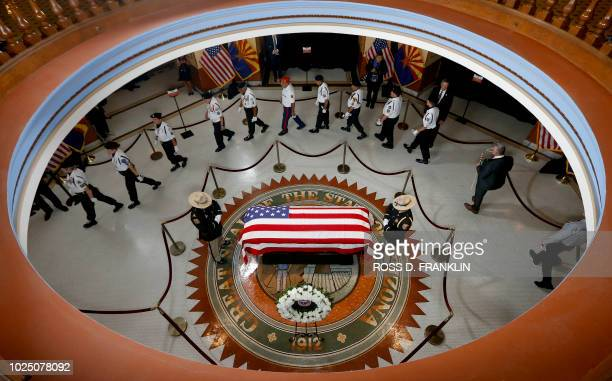 Veterans walk past the casket of the late US Senator John McCain during a memorial service at the Arizona Capitol on August 29, 2018 in Phoenix,...