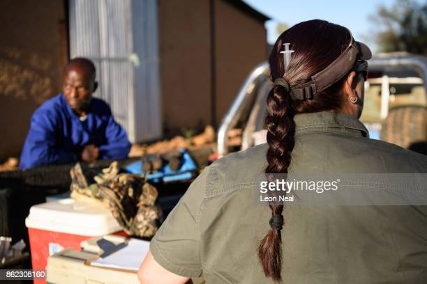 Veterinarian Michelle Otto wears a syringe in her hair as she prepares the tranquiliser darts ahead of a day of horn trimming at the ranch of rhino...