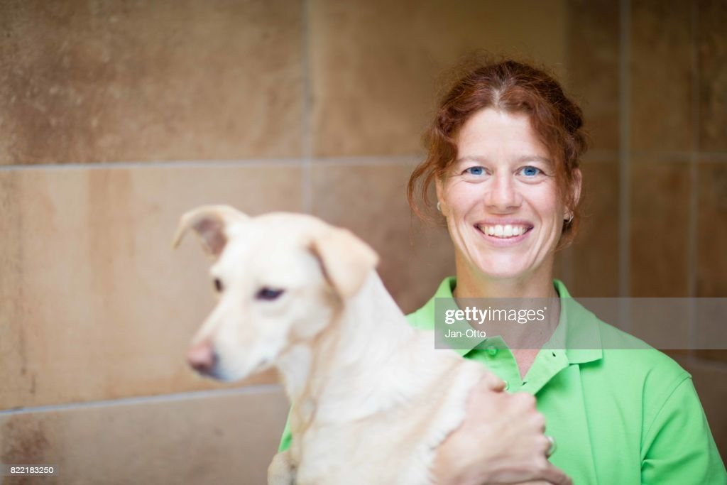 Veterinarian smiling with dog : Stock Photo