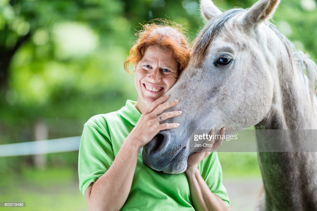 Veterinarian smiling with horse : Stock Photo