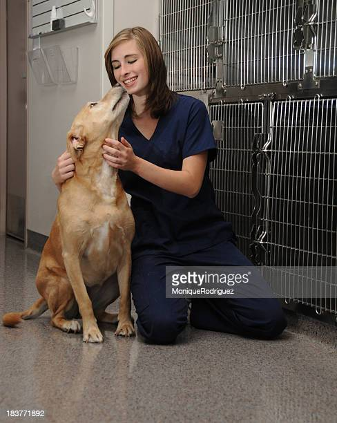 Veterinary nurse petting a dog outside of the kennels