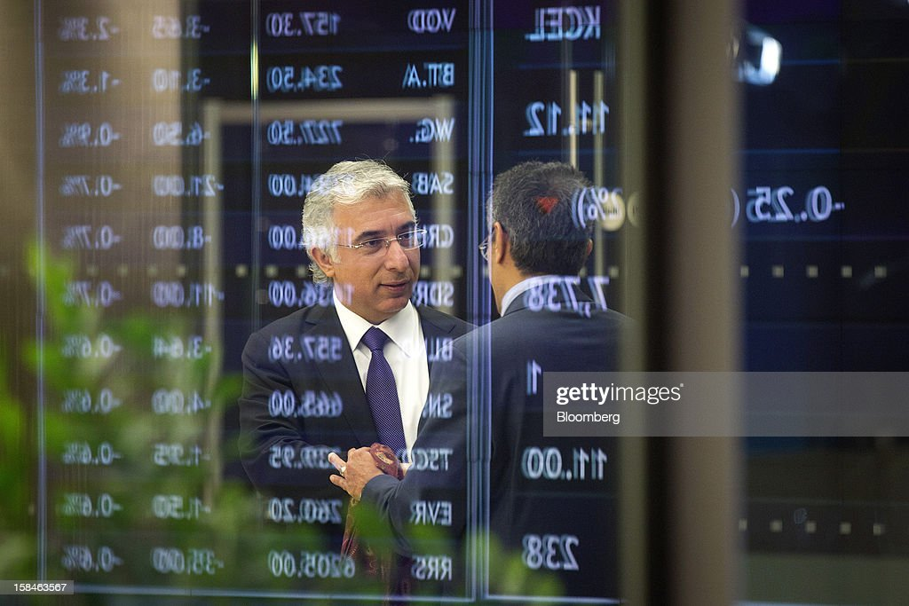 Veysel Aral, chief executive officer of Kcell, a unit of TeliaSonera AB, left, is reflected in an electronic share information display board, during the launch of the company's initial public offering (IPO) at the London Stock Exchange in London, U.K., on Monday, Dec. 17, 2012. Kcell, which has 11.6 million subscribers, is the largest operator in Kazakhstan with a subscriber market share of about 48 percent and a revenue market share of 57 percent, Aral said. Photographer: Simon Dawson/Bloomberg via Getty Images