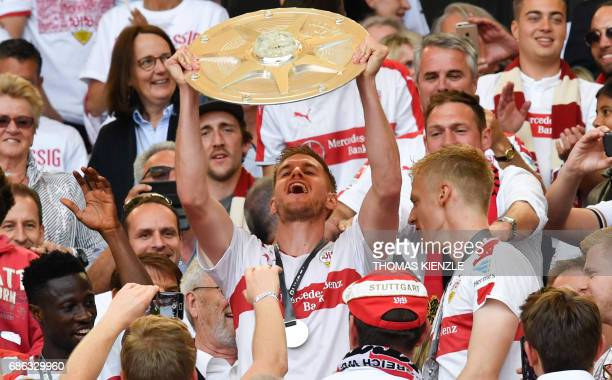 VfB Stuttgart's forward Simon Terodde holds up the trophy for the championship title after the German second division Bundesliga football match VfB...