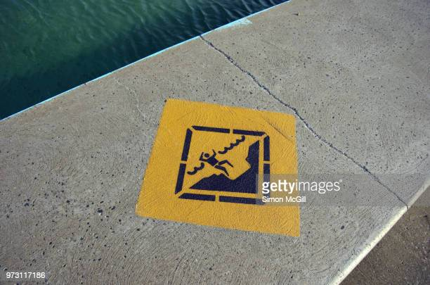Viable depth warning sign on the concrete edge of Coledale Rock Pool, Coledale, New South Wales, Australia