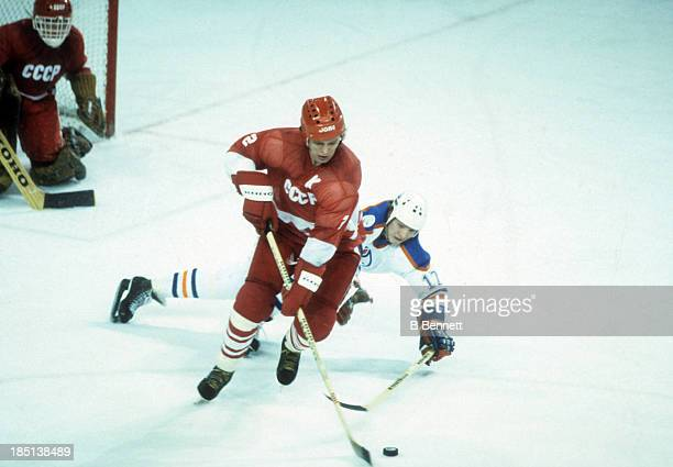 Viacheslav Fetisov of the USSR skates with the puck as Jari Kurri of the Edmonton Oilers dives to poke check the puck away during the 198283 Super...
