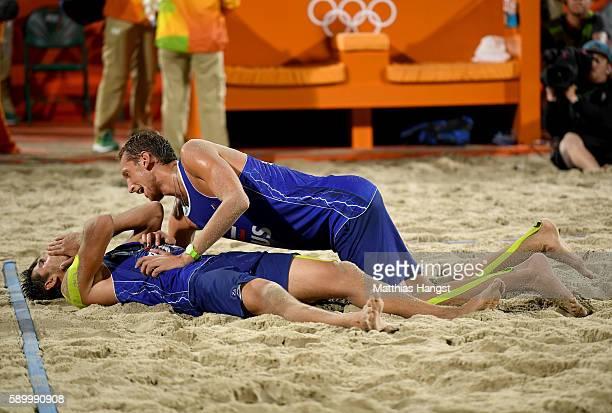 Viacheslav Krasilnikov and Konstantin Semenov of Russia celebrates after winning the Men's Beach Volleyball Quarterfinal match between the Russia and...