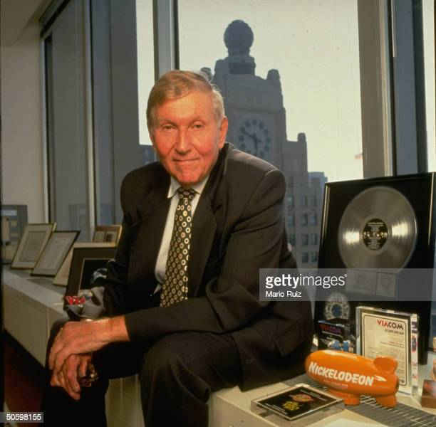 Viacom Inc chmn Sumner Redstone in office w paraphernalia fr various co divisions incl plastic blimp bearing Nickelodeon cable TV station logo