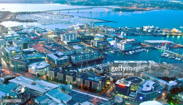 viaduct harbour at dush with auckland harbour bridge in background - waitemata harbor stock photos and pictures
