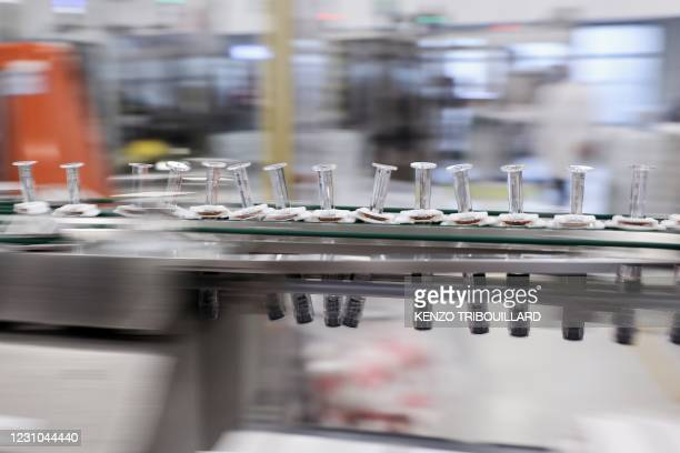 Vials are seen on a packing line at the factory of British pharmaceutical company GlaxoSmithKline in Wavre on February 8, 2021 where the Covid-19...