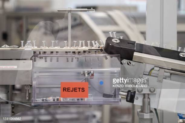 Vials are seen on a packing line of the factory of British pharmaceutical company GlaxoSmithKline in Wavre on February 8, 2021 where the Covid-19...