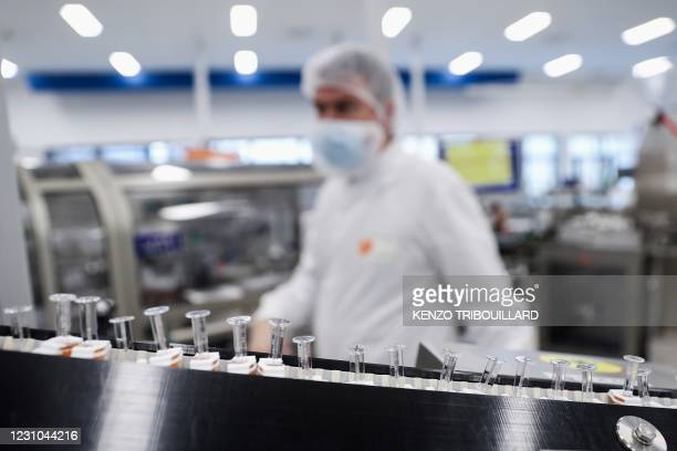 Vials are seen on a production line at the factory of British pharmaceutical company GlaxoSmithKline in Wavre on February 8, 2021 where the Covid-19...