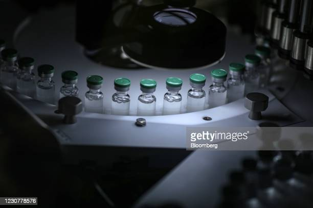 Vials of Covishield, the local name for the Covid-19 vaccine developed by AstraZeneca Plc. And the University of Oxford, move along a conveyor on the...