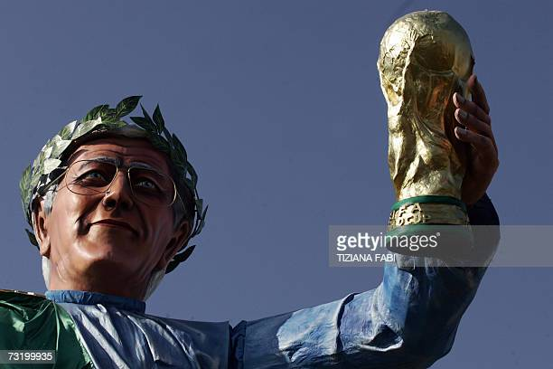 A giant carnival mask representing the former coach of the Italian team Marcello Lippi carrying the Wold Cup trophy parades through the streets of...