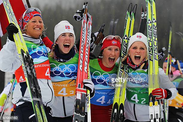Vibeke W Skofterud Kristin Stoermer Steira Marit Bjoergen and Therese Johaug of Norway celebrate after winning the gold medal during the Ladies'...
