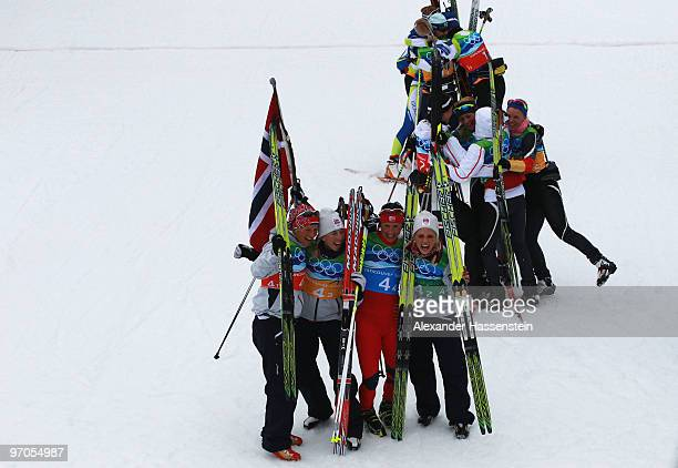 Vibeke W Skofterud Kristin Stoermer Steira Marit Bjoergen and Therese Johaug of Norway celebrate after winning the gold medal with silver medalists...