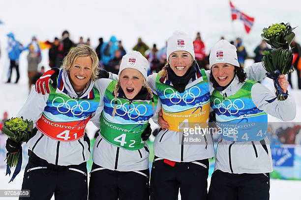 Vibeke W Skofterud Therese Johaug Kristin Stoermer Steira and Marit Bjoergen of Norway celebrate after winning the gold medal during the Ladies'...