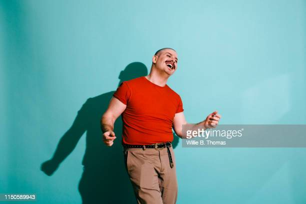 vibrance portrait of man dancing - blue trousers stock pictures, royalty-free photos & images