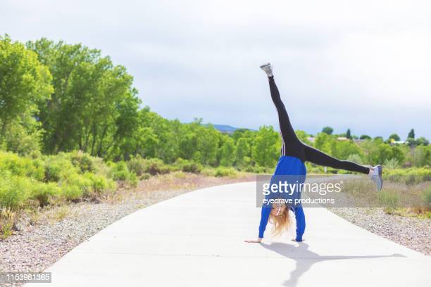 vibrant and lively generation z female experiencing exaggerated fun and excitement outdoors in western colorado on a sunny day - cartwheel stock pictures, royalty-free photos & images
