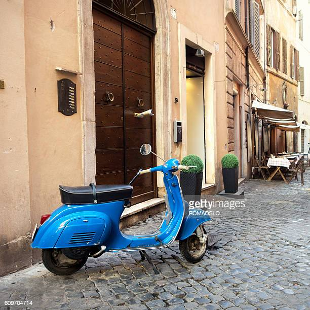Vibrant Blue scooter patked in a  Roman alley, Rome Italy