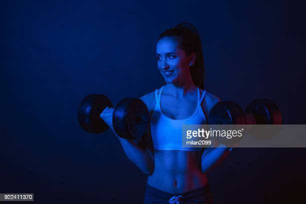 Vibrant color portrait with red and blue lights of a woman exercising in studio