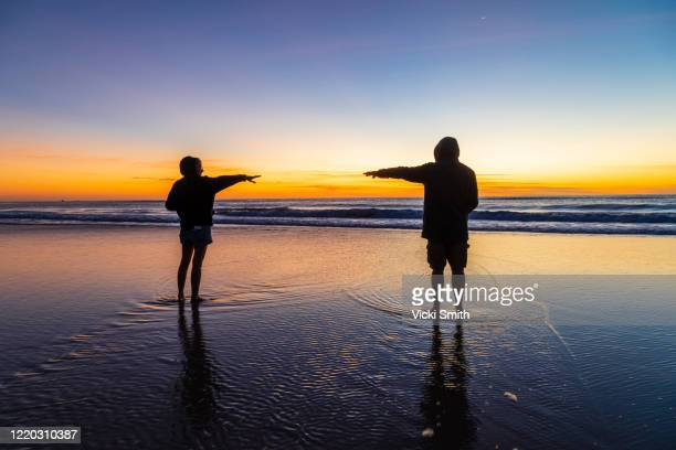 vibrant colored sunrise over the ocean with a silhouette of a adult male and female - temas sociales fotografías e imágenes de stock