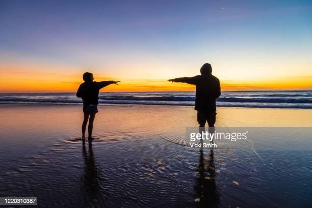 vibrant colored sunrise over the ocean with a silhouette of a adult male and female - questão social imagens e fotografias de stock
