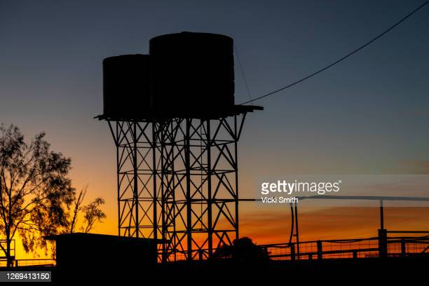 vibrant colored sunset outback australia with water tanks silhouetting the sky - water tower storage tank stock pictures, royalty-free photos & images