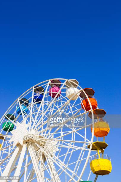 Vibrant colorful ferris wheel against clear blue sky in Barcelona, Spain