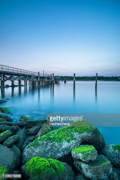 vibrant colors light up the sky just after sunset over a long fishing pier - jones beach stock pictures, royalty-free photos & images