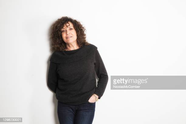 vibrant female in her early 60s excited studio portrait with turtleneck sweaters and hand in pocket - big hair stock pictures, royalty-free photos & images