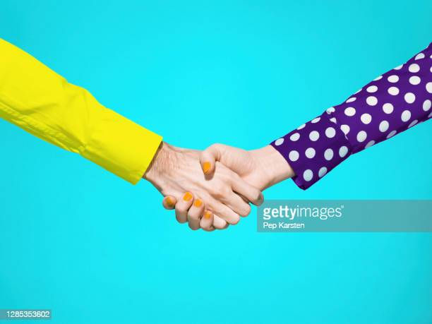 vibrant handshake on turquoise background - printed sleeve stock pictures, royalty-free photos & images