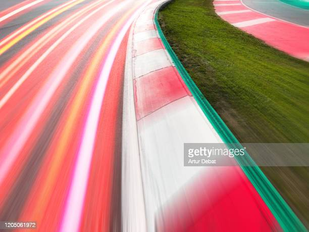 vibrant long exposure light trail of speed cars competing in circuit. - sports track stock pictures, royalty-free photos & images