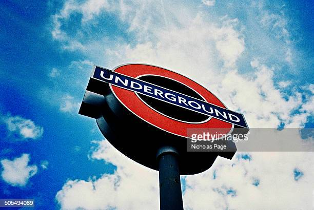 Vibrant low angle image of a London Underground sign. Taken on film and then cross processed. In the background a deep blue sky.