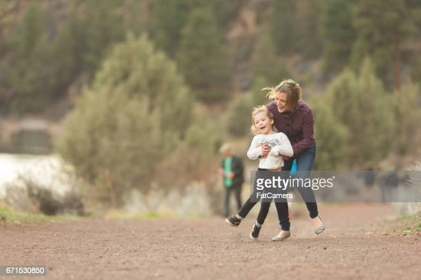Vibrant mom chases down her young daughter playfully out in nature