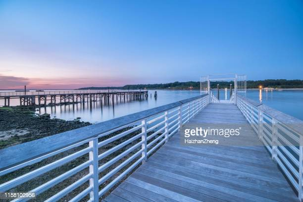 vibrant pink and orange sunset over a fishing pier and rock jetty. - long island stock pictures, royalty-free photos & images