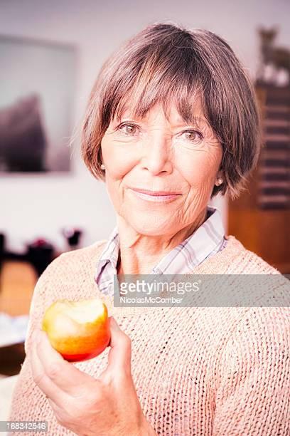 Vibrant Senior woman eating an Apple