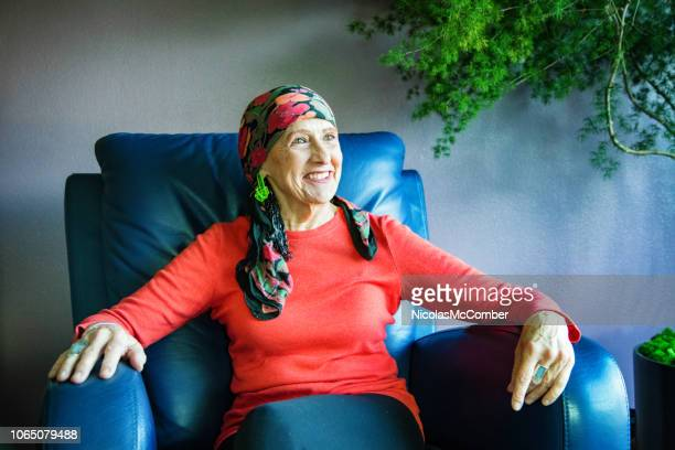vibrant senior woman wearing a head scarf smiling in her living room - reclining chair stock photos and pictures