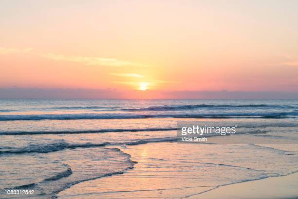 vibrant sunrise over the ocean - zonsopgang stockfoto's en -beelden