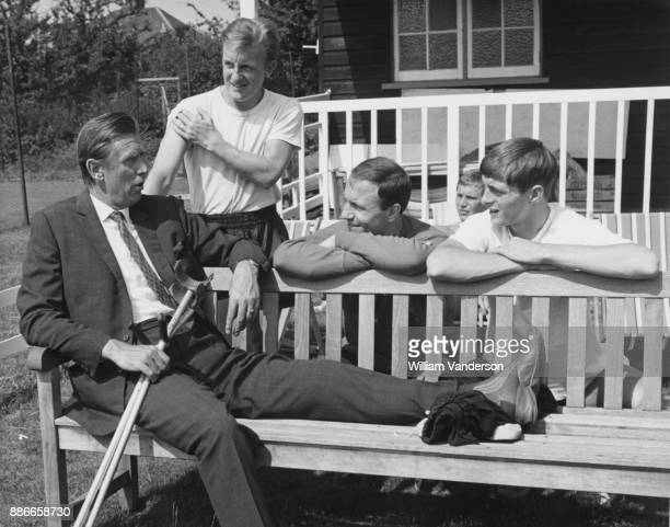 Vic Buckingham manager of Fulham FC talks to Fulham players Terry Dyson George Cohen and Allan Clarke after a training session at a ground in Ewell...