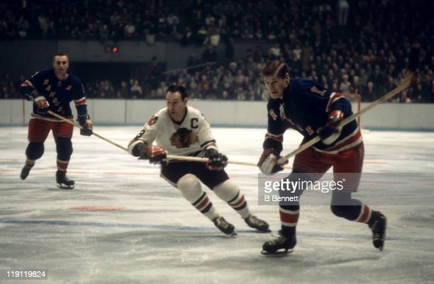 Vic Hadfield of the New York Rangers skates on the ice as Pierre Pilote of the Chicago Blackhawks follows behind as Harry Howell of the Rangers looks...