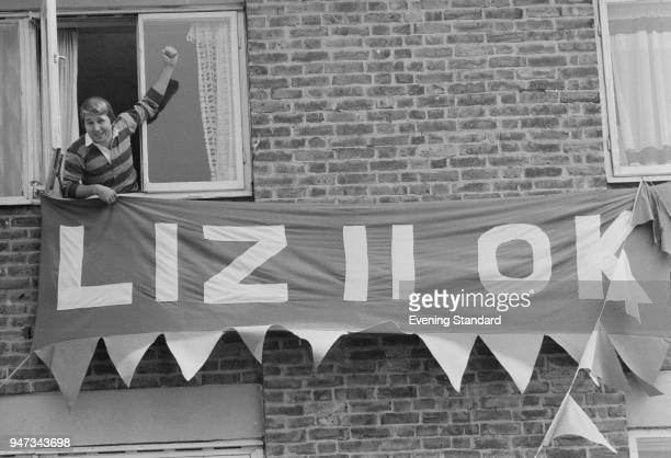 Vic Hiscoke looking out a window shows his banner which says 'Liz II OK' on the occasion of the Silver Jubilee of Queen Elizabeth II UK 3rd June 1977