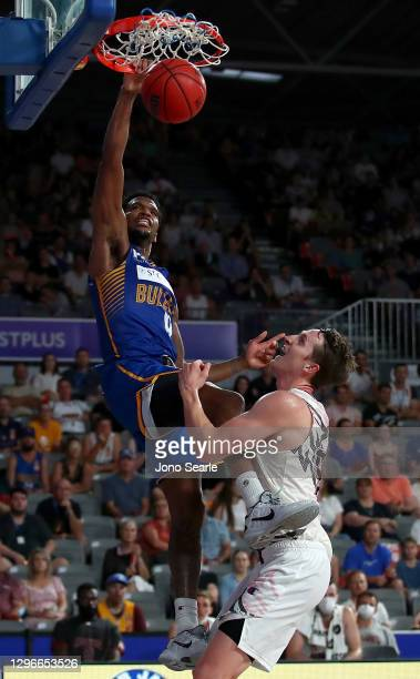 Vic Law of the Bullets dunks over Cameron Bairstow of the Hawks during the round one NBL match between the Brisbane Bullets and the Illawarra Hawks...