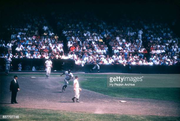Vic Power of the Cleveland Indians rounds second as Rocky Bridges of the Detroit Tigers makes sure he touches second during an MLB game on July 5...